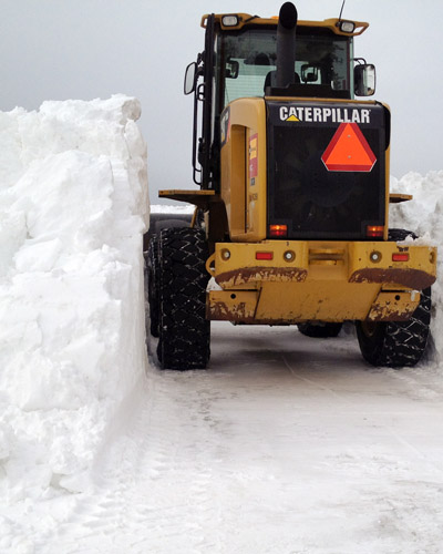 Snowline Alaska operates heavy equipment to deal with a large snow drift on a commercial property