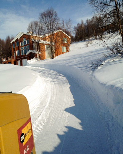 Snowline Alaska's tractor snow blowers at work removing snow from a hillside residential driveway