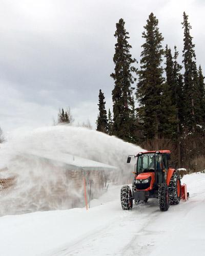 Snowline Alaska clear snow from an Anchorage hillside driveway after a heavy snowfall
